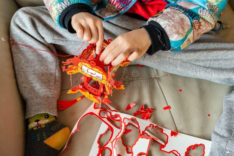 Bambino che fa una lanterna del cinese tradizionale per il nuovo anno sui suoi propri immagini stock