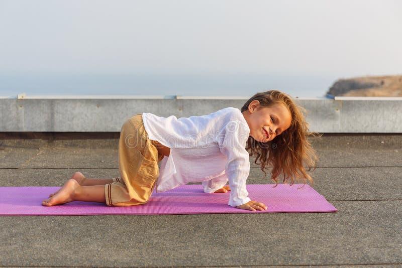Bambino che fa yoga sul tetto fotografia stock libera da diritti