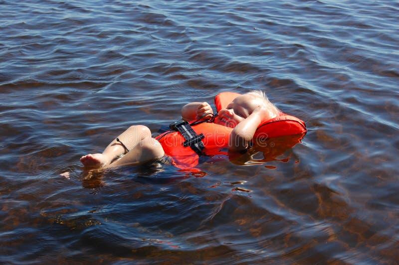 Bambino che galleggia con la maglia di vita fotografia stock