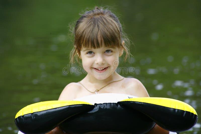 Bambino che galleggia su un tubo interno fotografia stock