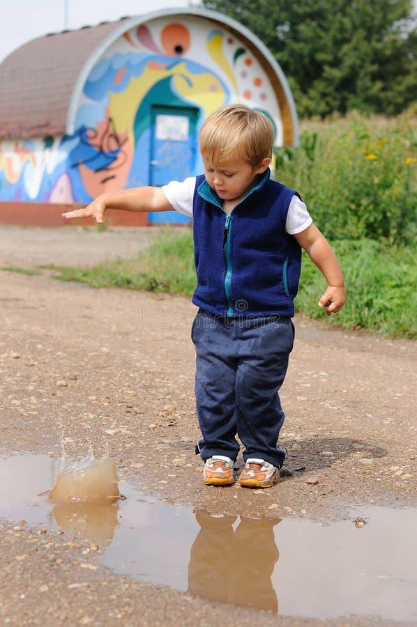 Bambino che getta piccola pietra per riunirsi immagine stock