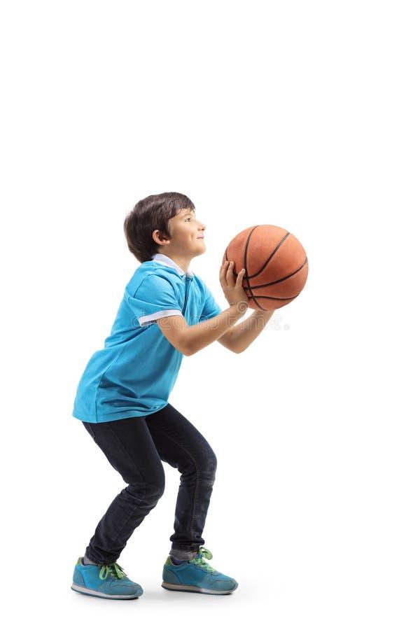 Bambino che getta una pallacanestro immagini stock