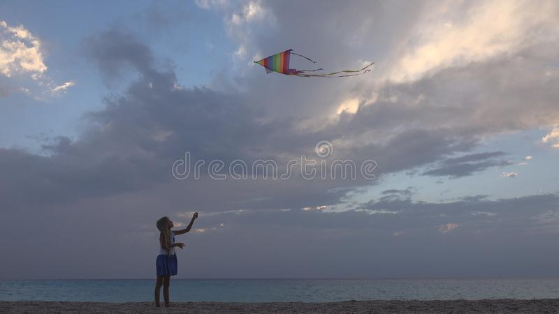 Bambino che gioca aquilone volante sulla spiaggia al tramonto, bambina felice sulla linea costiera immagini stock libere da diritti