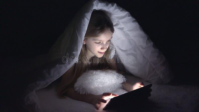 Bambino che gioca compressa nella notte scura, Internet di lettura rapida della ragazza a letto, non dormendo fotografia stock libera da diritti