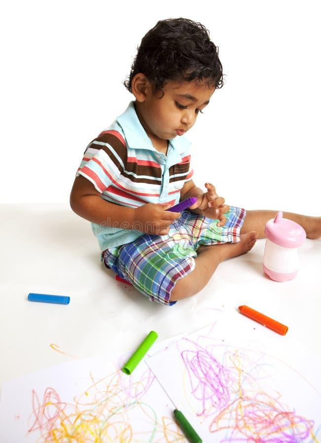 Bambino che gioca con i pastelli immagini stock libere da diritti
