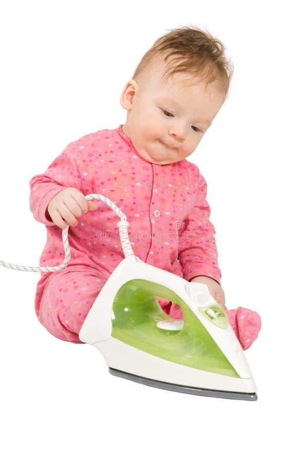 Bambino che gioca con il ferro da stiro fotografia stock