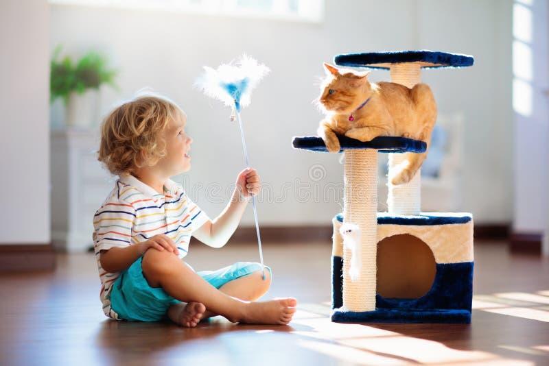 Bambino che gioca con il gatto a casa Bambini ed animali domestici immagini stock libere da diritti