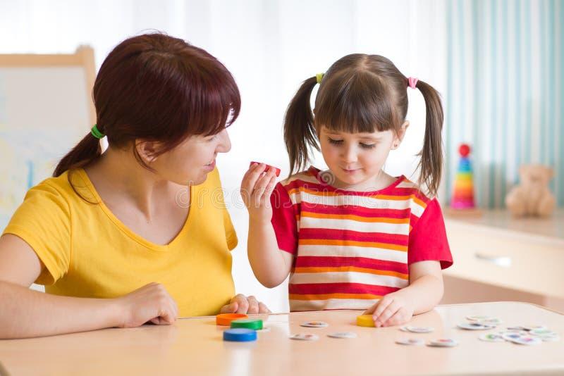 Bambino che gioca con il logopedista immagini stock
