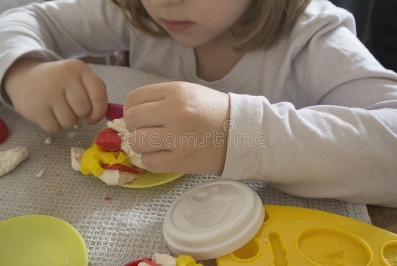 Bambino che gioca con il plasticine fotografia stock