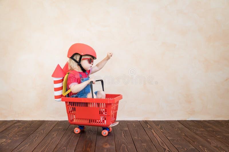 Bambino che gioca con il razzo del giocattolo a casa fotografie stock