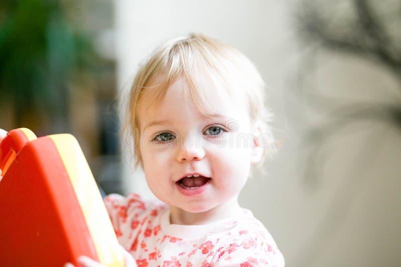 Bambino che gioca con il sorriso felice dei giocattoli immagini stock