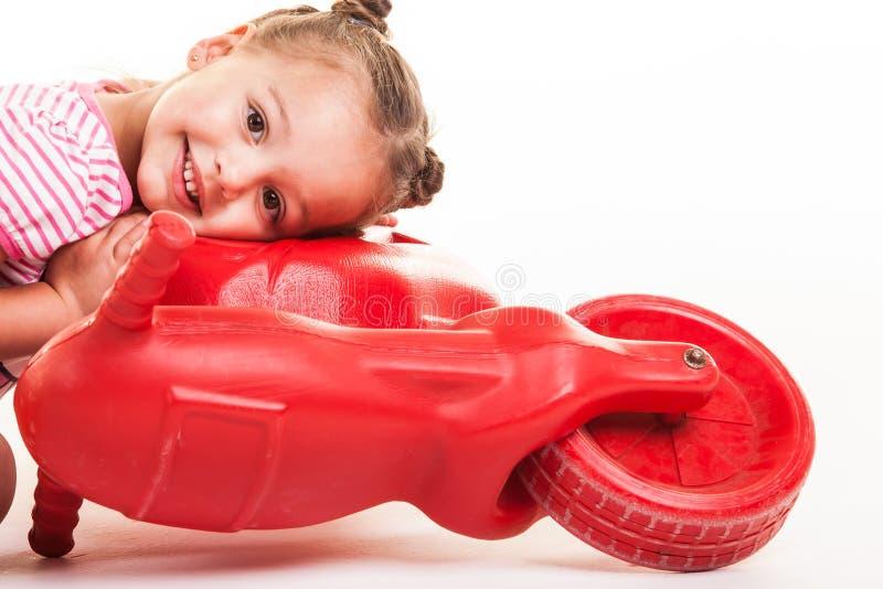 Bambino che gioca con il suo motorino rosso immagine stock