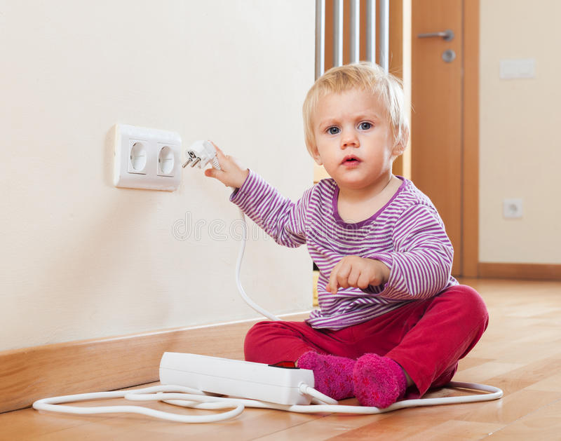 Bambino che gioca con l'estensione elettrica fotografia stock