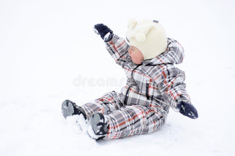 Bambino che gioca con la neve nell'inverno immagini stock