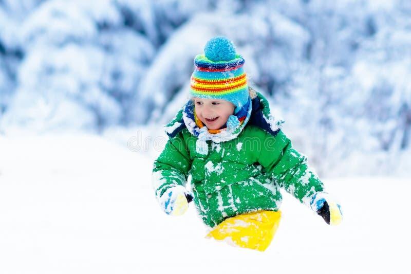 Bambino che gioca con la neve nell'inverno Bambini all'aperto fotografie stock libere da diritti