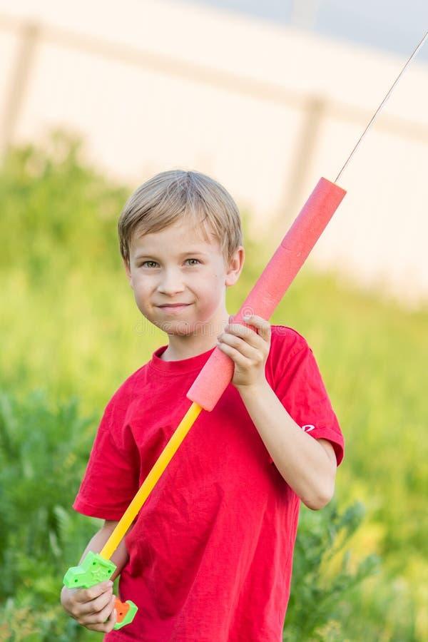 Bambino che gioca con la pistola a acqua fotografie stock libere da diritti