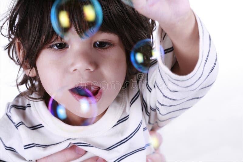 Bambino che gioca con le bolle immagini stock