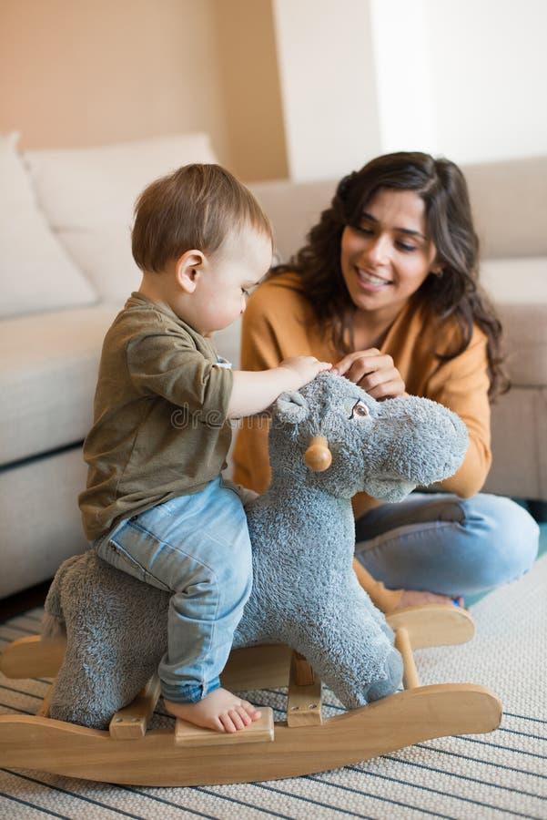 Bambino che gioca con un cavallo a dondolo fotografia stock