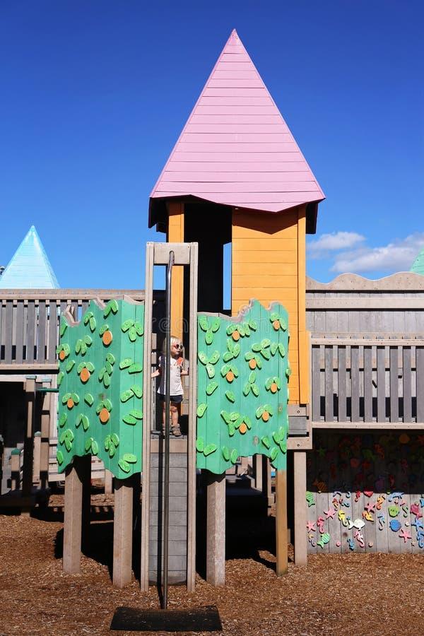 Bambino che gioca dentro il castello del campo da giuoco su Sunny Summer Day fotografia stock libera da diritti