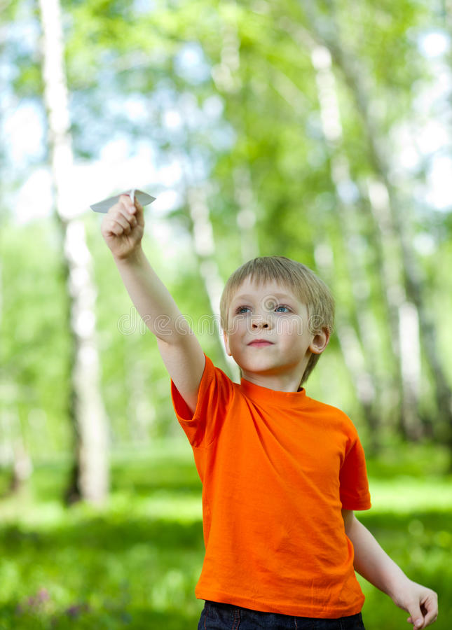 Bambino che gioca e che pilota un aeroplano di carta fotografia stock