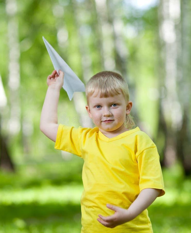 Bambino che gioca e che pilota un aeroplano di carta fotografia stock libera da diritti