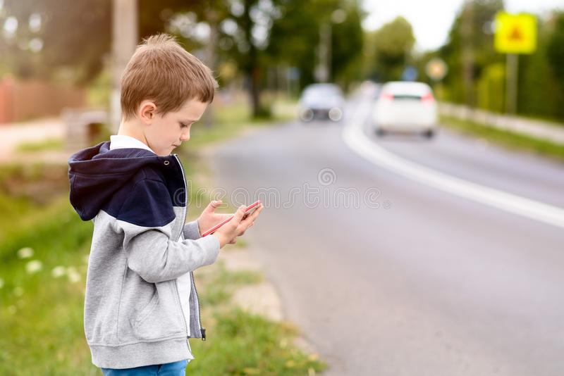 Bambino che gioca i giochi mobili sullo smartphone sulla via immagini stock libere da diritti