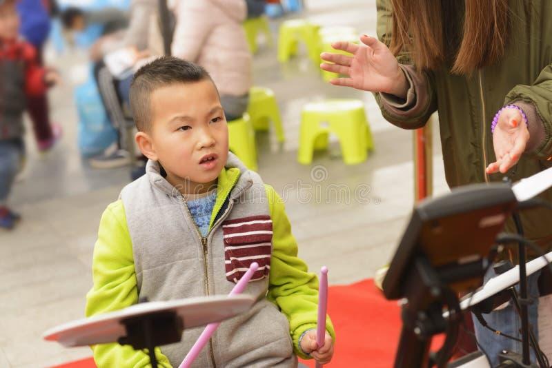 Bambino che gioca lo strumento di percussione alla via fotografie stock