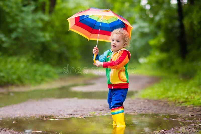 Bambino che gioca nella pioggia sotto l'ombrello fotografia stock libera da diritti