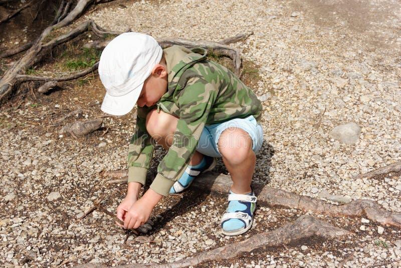 Bambino che gioca nella sabbia con i ciottoli fotografia stock