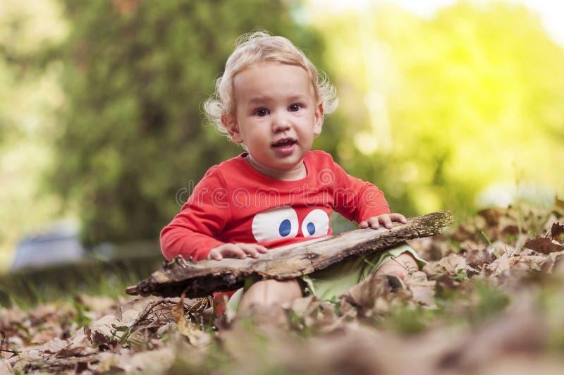 Bambino che gioca nelle foglie fotografia stock libera da diritti