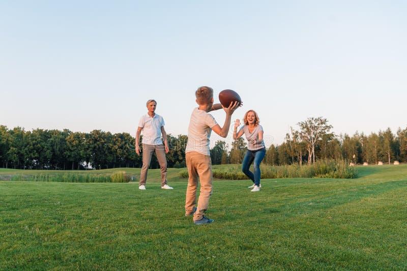 Bambino che gioca rugby con i nonni fotografia stock