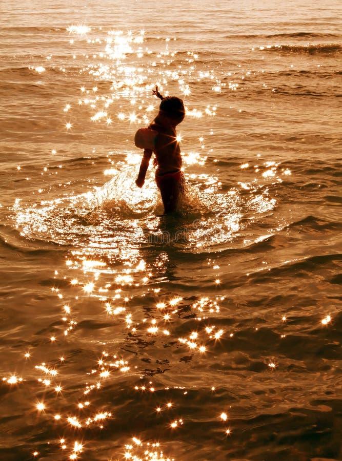Bambino che gioca in stelle dell'acqua al tramonto immagini stock