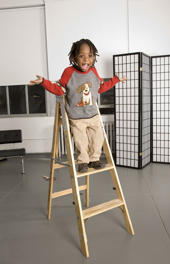 Bambino che gioca su una scaletta immagini stock