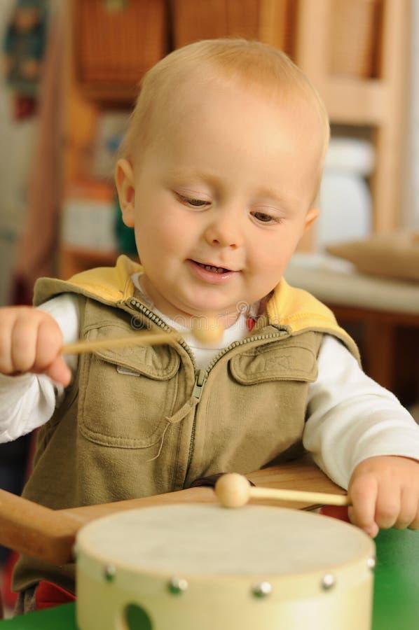 Bambino che gioca sul tamburo fotografia stock libera da diritti