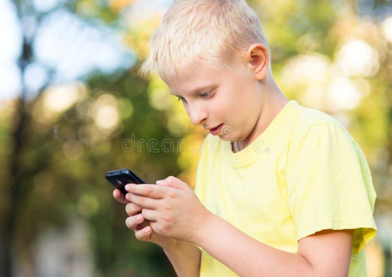 Bambino che gioca sul vostro smartphone fotografia stock libera da diritti