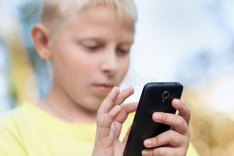 Bambino che gioca sul vostro smartphone immagine stock