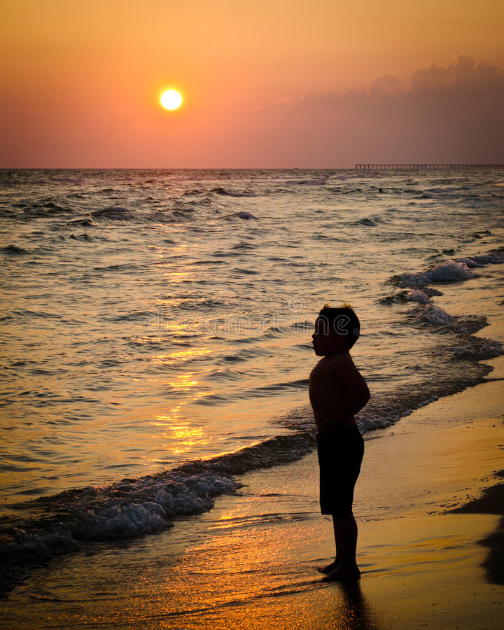 Bambino che gioca sulla spiaggia fotografia stock