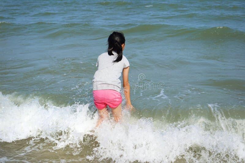 Bambino che gioca sulla spiaggia con luce solare nelle vacanze estive immagine stock