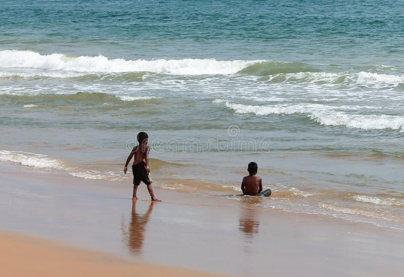 Bambino che gioca sulla spiaggia del mare fotografia stock libera da diritti