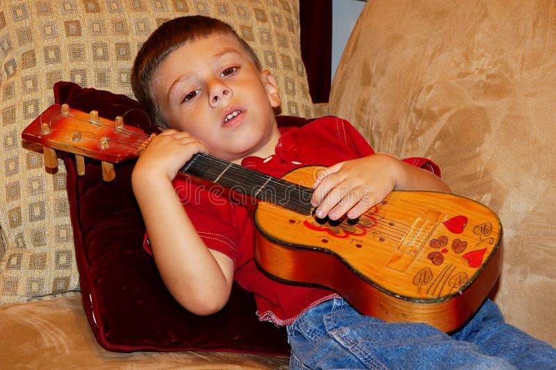 Bambino che gioca un Ukulele fotografia stock libera da diritti