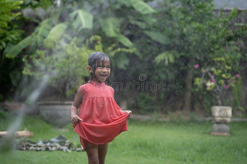Bambino che gode del gioco con la spruzzata dell'acqua in giardino fotografia stock libera da diritti