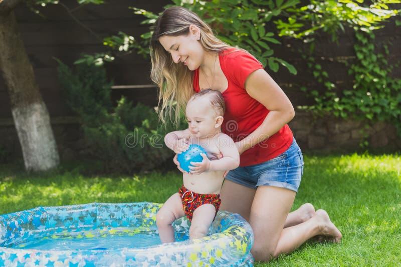 Bambino che gode del nuoto nello stagno al giardino con la giovane madre fotografie stock
