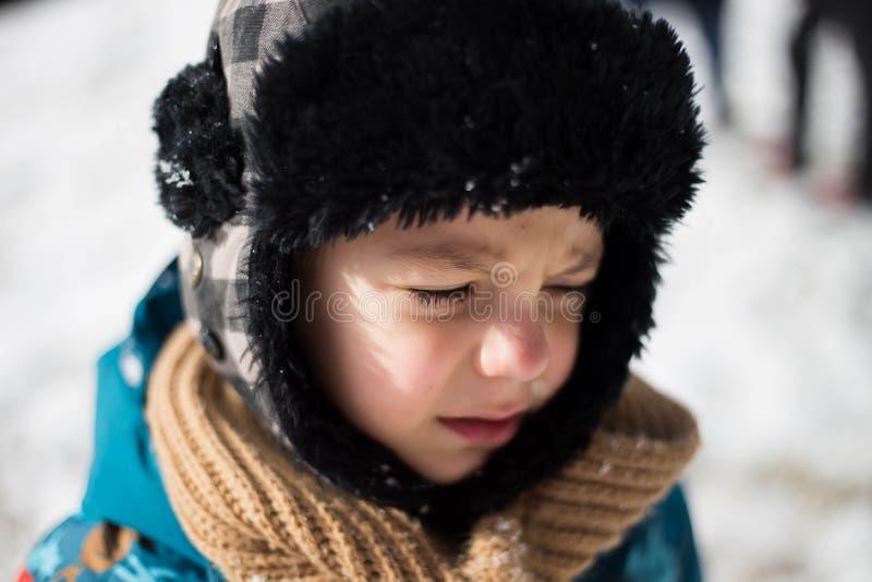 Bambino che grida dopo essere stato colpito nel fronte con una palla di neve immagine stock libera da diritti
