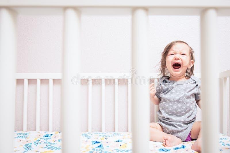Bambino che grida in greppia fotografia stock