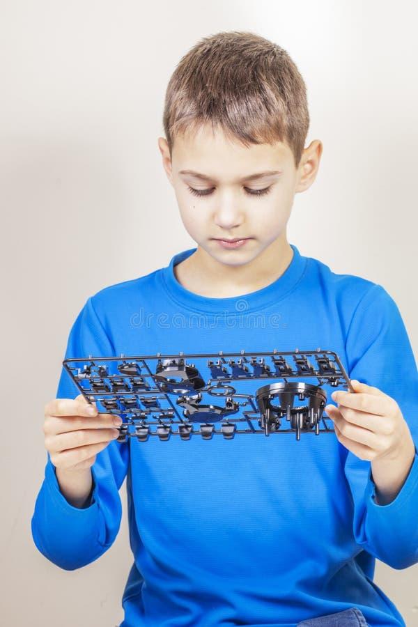 Bambino che guarda ai nuovi dettagli dell'automobile del robot Robot, imparando, tecnologia, istruzione del gambo per il fondo de fotografie stock libere da diritti