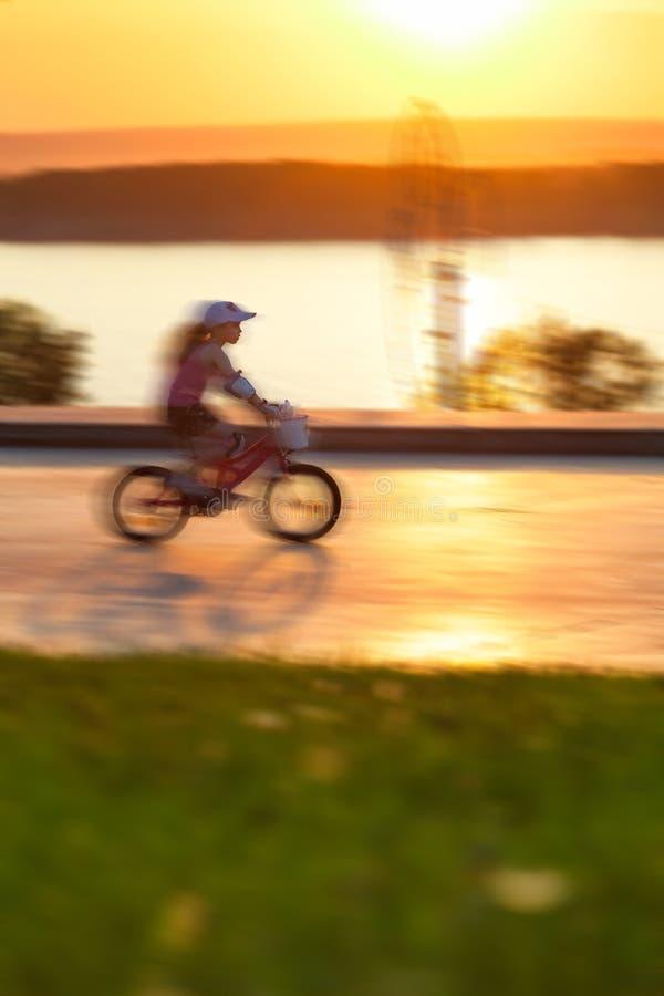 Bambino che guida una bici lungo il fiume fotografie stock