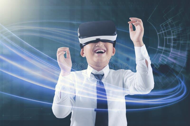 Bambino che impara con la sua cuffia avricolare di realtà virtuale immagine stock