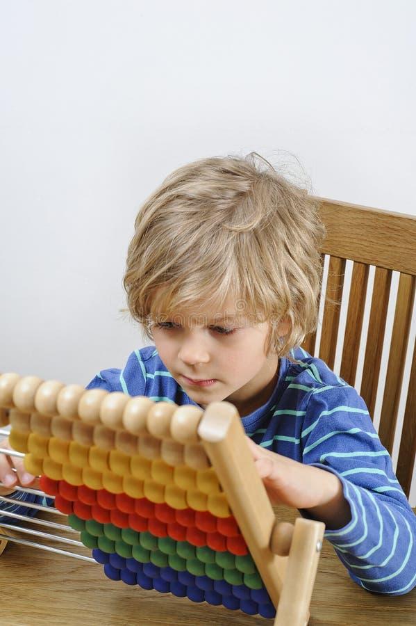Bambino che impara contare su un abaco immagini stock libere da diritti