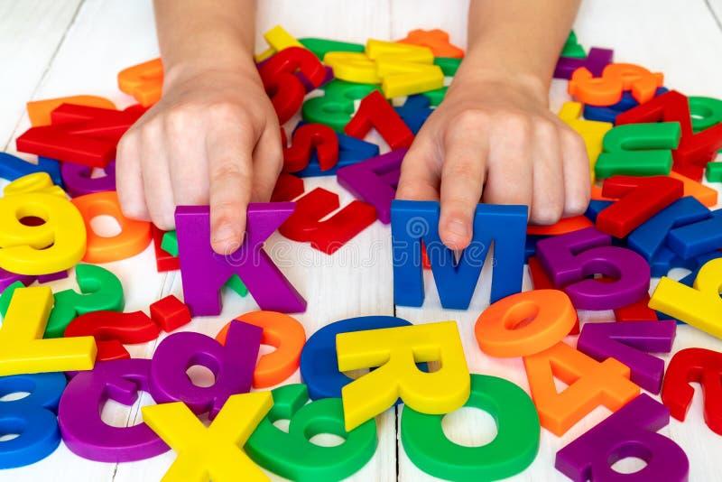 Bambino che impara facendo uso dei numeri e delle lettere magnetici fotografia stock libera da diritti