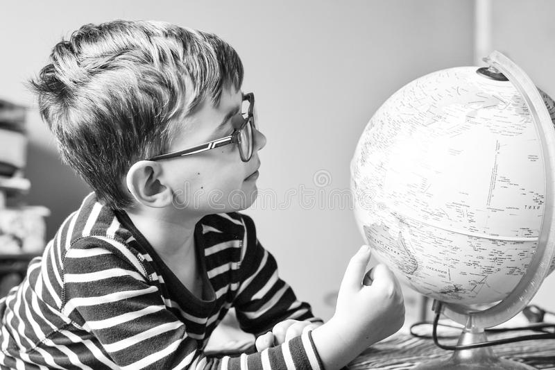 Bambino che impara geografia con il globo a casa fotografia stock libera da diritti